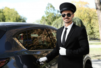 Young handsome driver opening luxury car door. Chauffeur service
