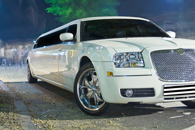 White stretch limousine by night